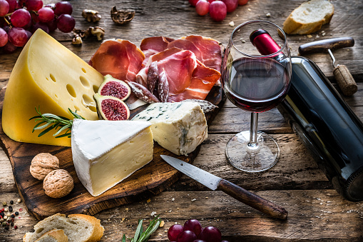 Appetizer: red wine, cheese and cured ham on rustic wooden table 1183169940