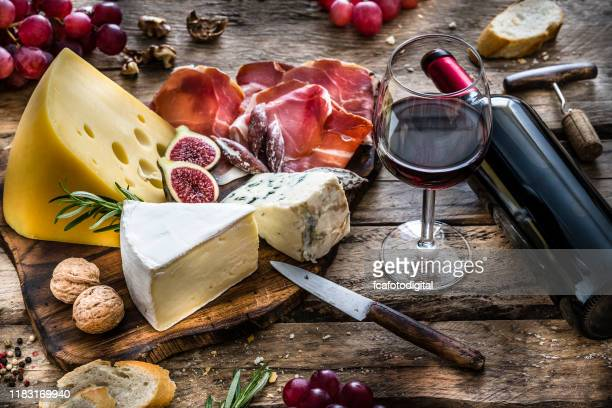 appetizer: red wine, cheese and cured ham on rustic wooden table - cheese stock pictures, royalty-free photos & images
