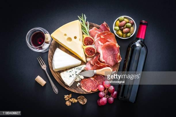 voorgerecht: rode wijn, gezouten ham en kaas op zwarte fond - wijnglas stockfoto's en -beelden