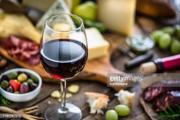 前菜:素朴な木製のテーブルの上に赤ワイングラス、チーズ、スペインのチョリソ - 赤ワイン ストックフォトと画像