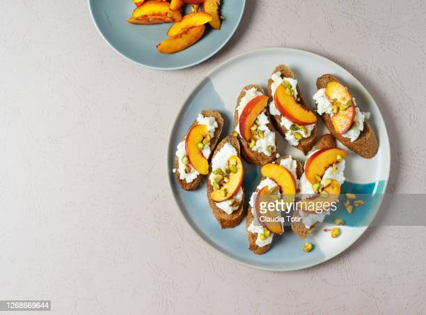 appetizer/canapé with peach an burrata on beige background - おかず系 ストックフォトと画像