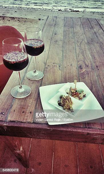 Appetizers And Red Wine Served On Wooden Table At Beach Restaurant
