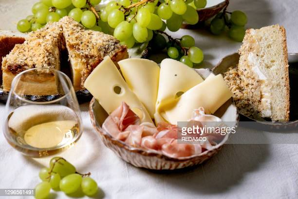 Appetizers antipasti with white sicilian focaccia. Traditional bread sliced cake with onion served with prosciutto ham. Cheese. Grapes and glass of...