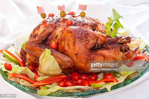 Appetizing crispy red roasted spicy grilled chicken with vegetable garnish on plate against white background