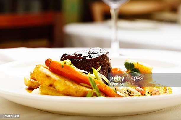 Appetizing restaurant entree of seared steak and glazed vegetables