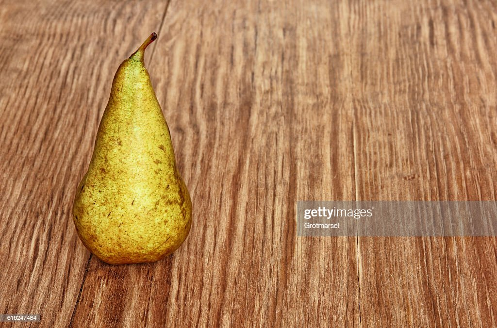 Appetizing sweet pear on grunge wooden background taken closeup. : Foto de stock