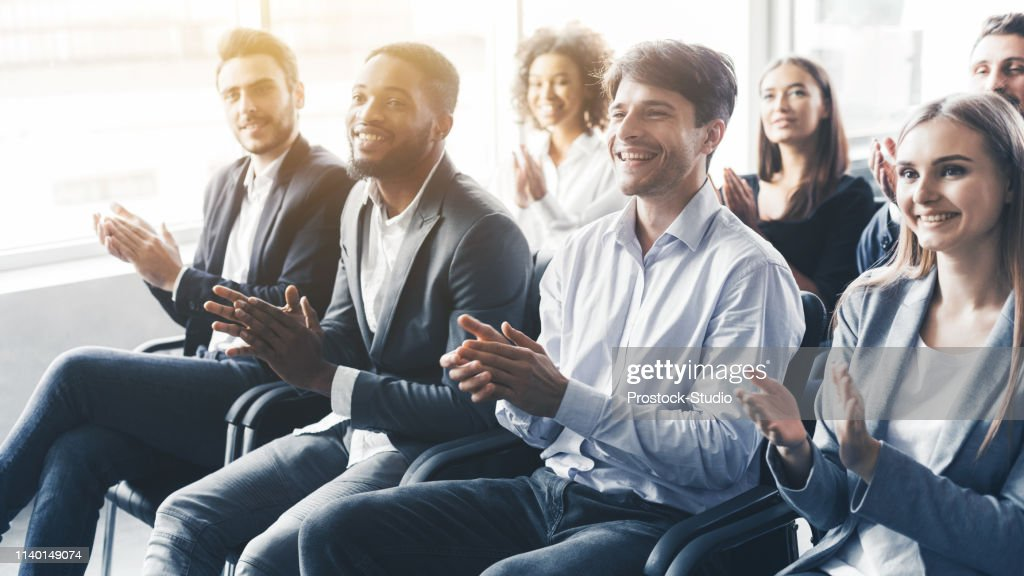 Applauding to speaker. Group of happy business people in conference hall : Stock Photo