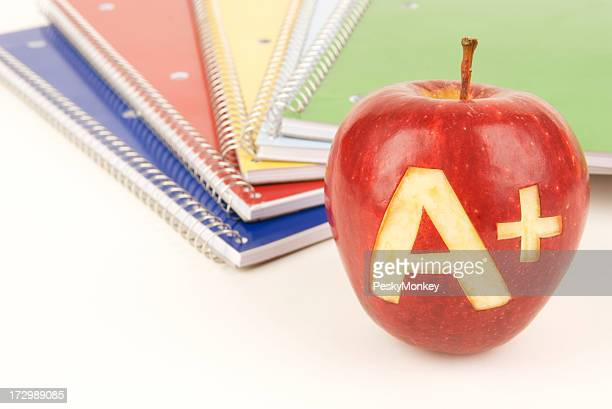 Apple A+ in front of Spiral Notebooks