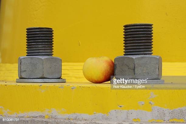 Apple Amidst Nut And Bolt Against Yellow Wall