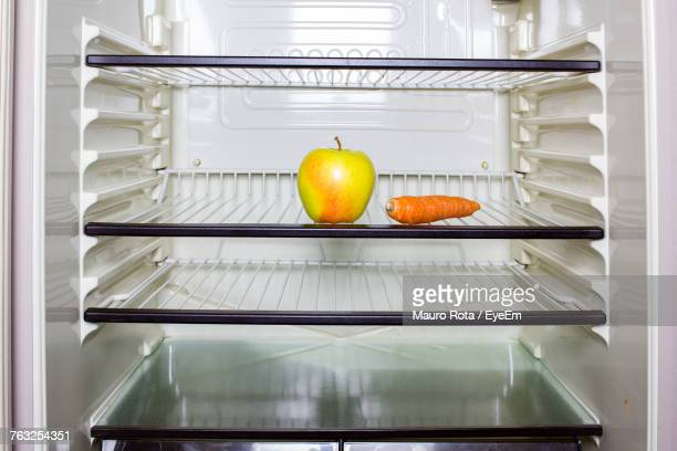 Apple And Carrot On Shelf In Refrigerator