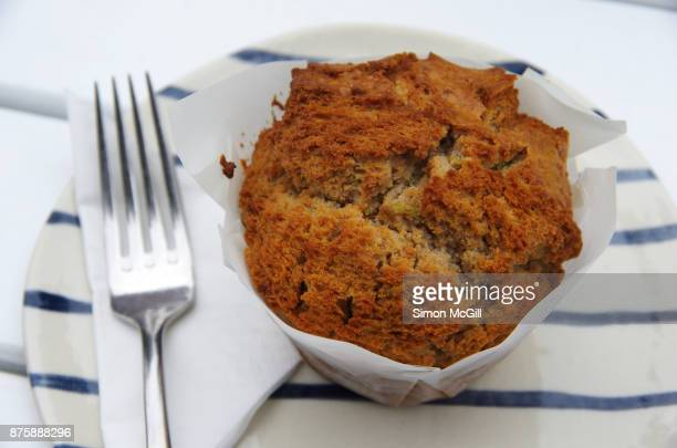 Apple and cinnamon muffin on a blue and white striped plate on a white outdoor table