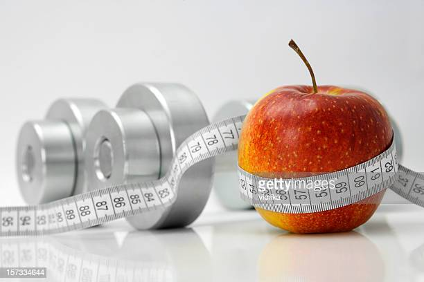Apple and gym accessories on white background