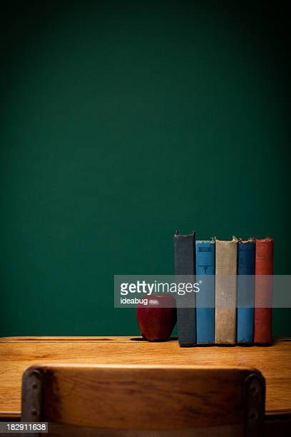 Apple and Old Books on School Desk by Chalkboard