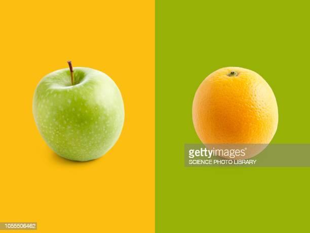 apple and orange against yellow and green background - vergleich stock-fotos und bilder