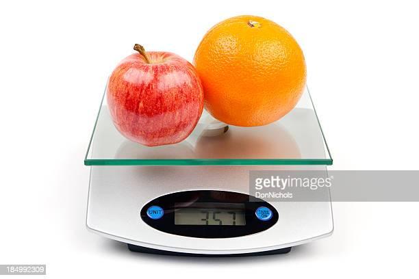 Apfel und Orange auf Waage