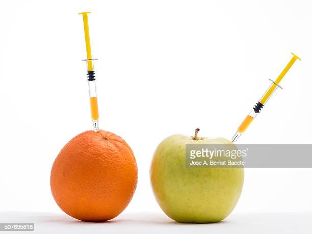 Apple and orange with a syringe stuck concept of transgenic foods