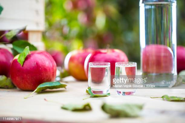 apple brandy distillate with apples on garden table - calvados stock pictures, royalty-free photos & images