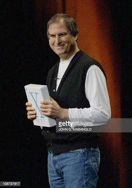 Apple CEO Steve Jobs holds a copy of Apple's new operating system Mac OS X during his keynote address at the World Wide Developers Conference in San...