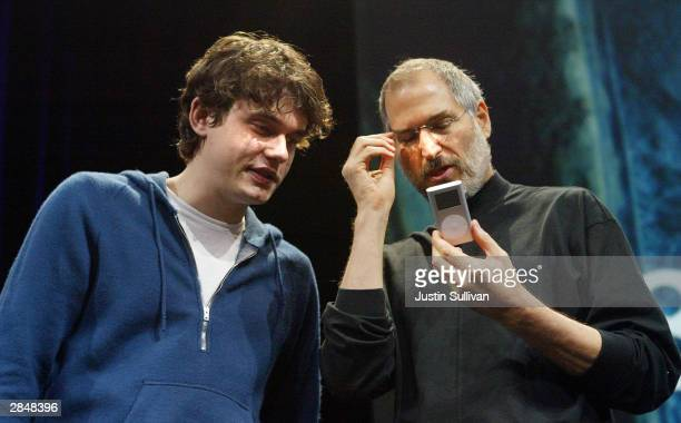 Apple CEO Steve Jobs looks at a new iPod mini with recording artist John Mayer at the Macworld expo January 6 2004 in San Francisco Jobs announced...