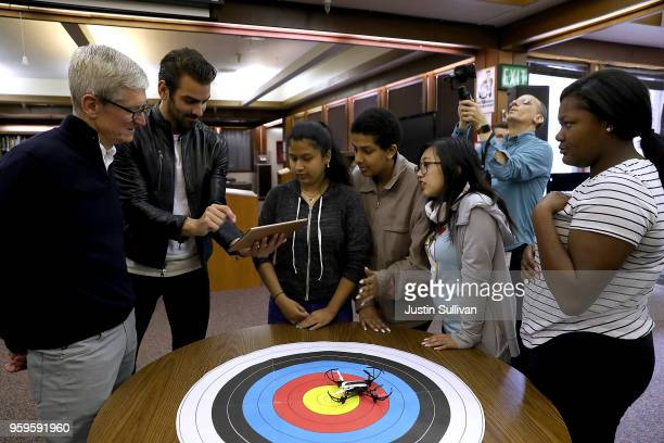 Apple CEO Tim Cook and actor model and activist for the deaf community Nyle DiMarco talk with students who are going to stage a demonstration with a...
