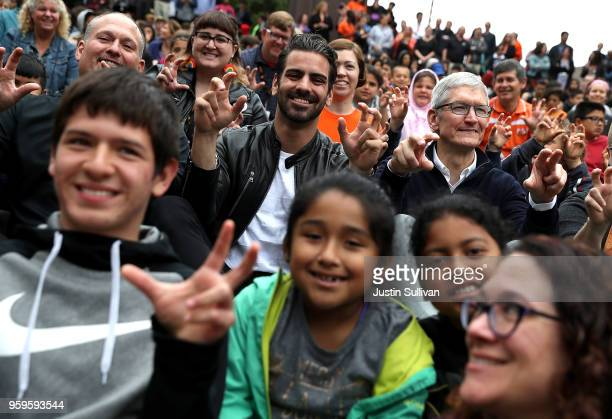 Apple CEO Tim Cook and actor model and activist for the deaf community Nyle DiMarco gesture while taking a picture with students at the California...