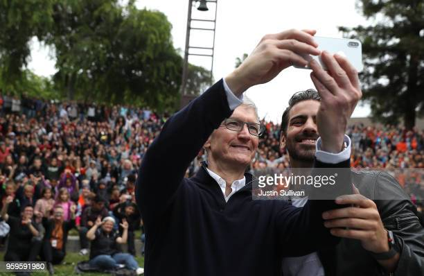 Apple CEO Tim Cook and cctor model and activist for the deaf community Nyle DiMarco take a selfie with students at the California School for the Deaf...