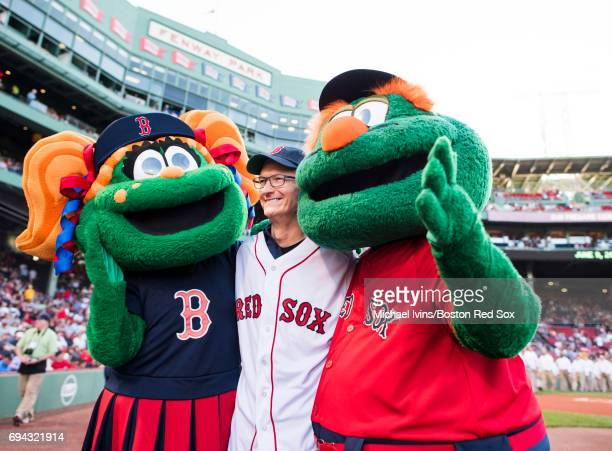 Apple CEO Tim Cook is surrounded by mascots Wally and Tessie before a game between the Boston Red Sox and the Detroit Tigers at Fenway Park on June 9...