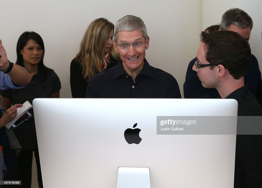 Apple CEO Tim Cook looks at the new 27 inch iMac with 5K retina display during an Apple special event on October 16, 2014 in Cupertino, California. Apple unveiled the new iPad Air 2 and iPad Mini 3 tablets and the iMac with 5K retina display.