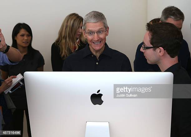 Apple CEO Tim Cook looks at the new 27 inch iMac with 5K retina display during an Apple special event on October 16 2014 in Cupertino California...