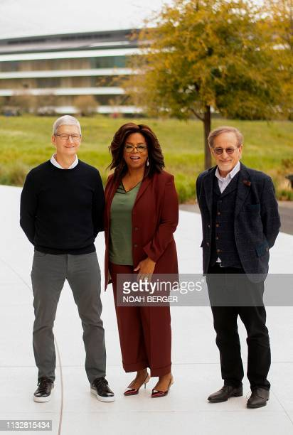 Apple CEO Tim Cook Oprah Winfrey and director Steven Spielberg stand for a photo during an event launching Apple tv at Apple headquarters on March 25...
