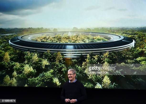 Apple CEO Tim Cook stands in front of a slide of the company's new campus which is under construction during a media event at Apple headquarters in...