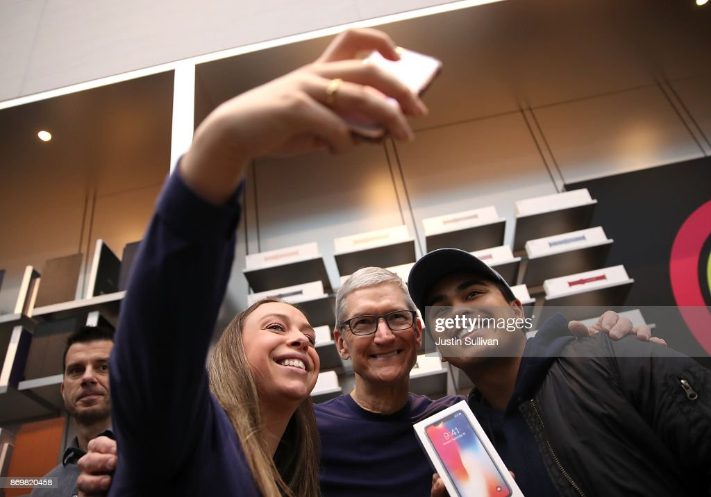 Apple CEO Tim Cook (C) takes a selfie with customers as the new iPhone X goes on sale at an Apple Store on November 3, 2017 in Palo Alto, California. The highly anticipated iPhone X went on sale around the world today.