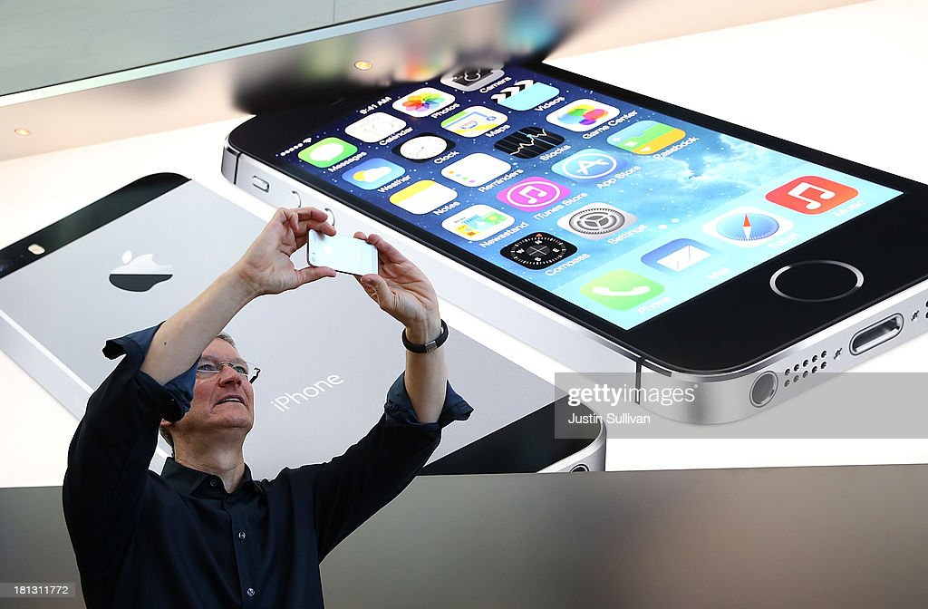 Apple CEO Tim Cook uses an iPhone to take a picture of customers waiting in front of an Apple store to purchase the new iPhones on September 20, 2013 in Palo Alto, California. Apple launched two new models of iPhone: the iPhone 5S, which is preceded by the iPhone 5, and a cheaper, paired down version, the iPhone 5C. The phones come with a new operating system.
