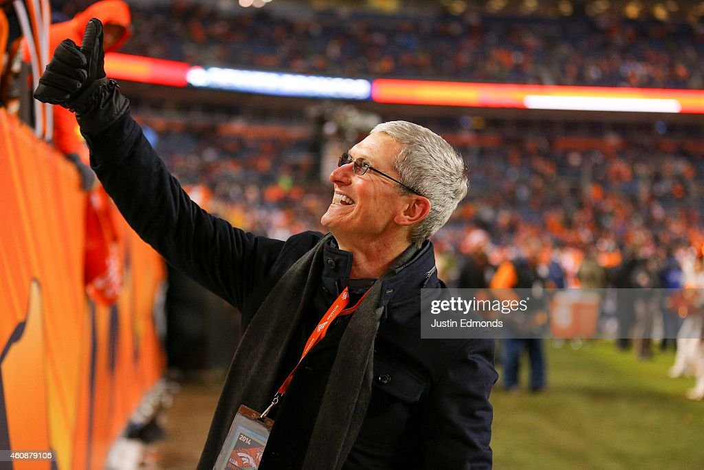 Apple CEO Tim Cook walks on the field and waives at fans after a game between the Denver Broncos and the Oakland Raiders at Sports Authority Field at Mile High on December 28, 2014 in Denver, Colorado.