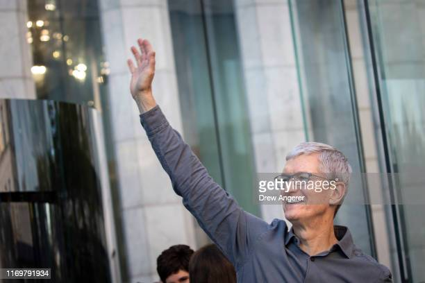 Apple CEO Tim Cook waves to customers before they enter Apple's flagship 5th Avenue store to purchase the new iPhone 11 on September 20 2019 in New...