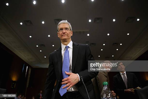 Apple CEO Timothy Cook returns from a break in his testimony before the Senate Homeland Security and Governmental Affairs Committee's Investigations...
