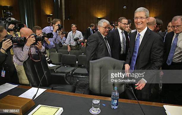 Apple CEO Timothy Cook smiles for photographers during a break in his testimony before the Senate Homeland Security and Governmental Affairs...