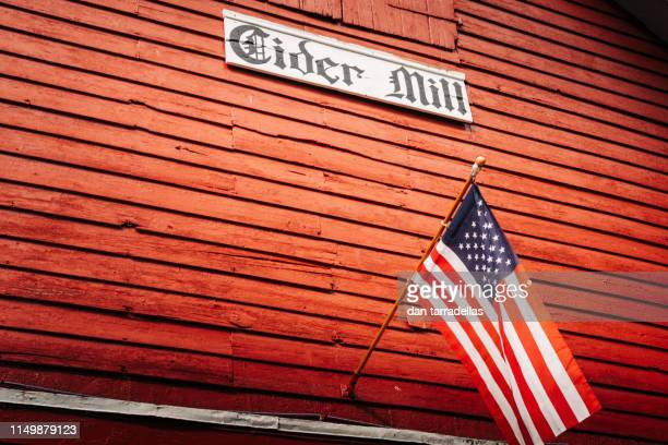 apple cider mill and american flag. - cider stock pictures, royalty-free photos & images