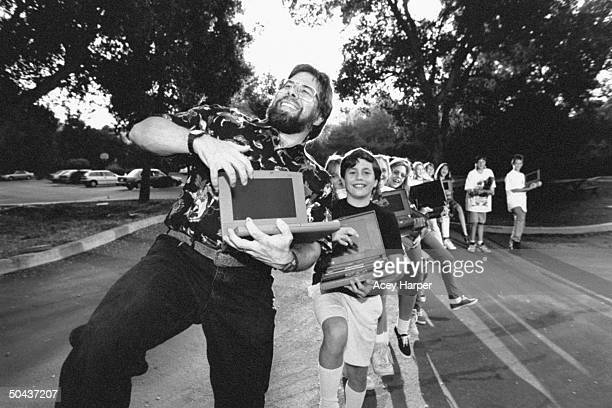 Apple Computer cofounder Steve Wozniak holding his Apple Macintosh Powerbook computer as he jubilantly leads a conga line of a dozen 6th 7th graders...