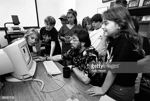 Apple Computer cofounder Steve Wozniak sitting in front of one of his Apple MacIntosh computers as a dozen 6th 7th graders stand around him while he...