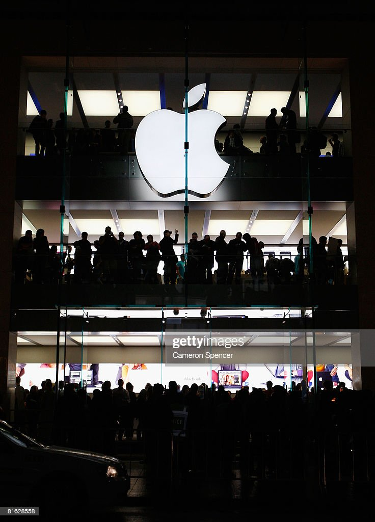 Apple customers look outside from various levels during the official