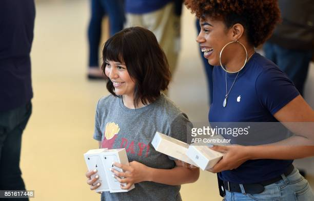 Apple customers smile for a photographer after purchasing newly released iPhones at an Apple store in San Francisco California on September 2017 /...