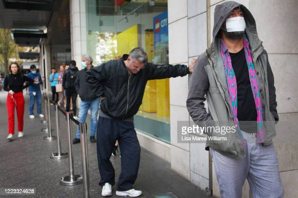 Apple customers social distance in a line outside the Apple Store at Bondi Junction on May 07, 2020 in Sydney, Australia. Apple stores across...