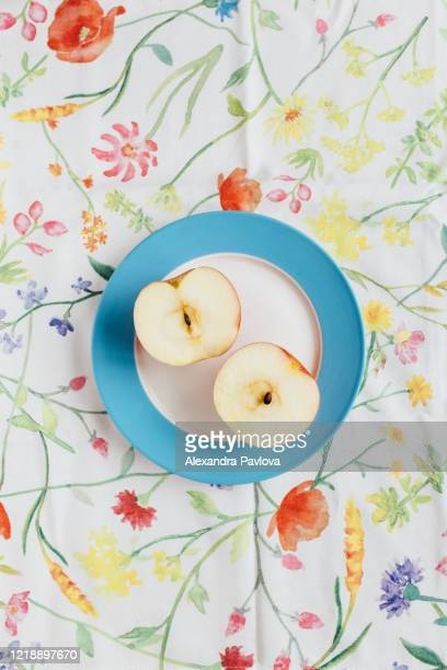 apple cut in half on a floral tablecloth - alexandra pavlova stock pictures, royalty-free photos & images