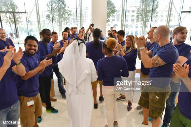 Apple employees cheer as the doors of the Dubai Mall Apple Store open for customers to purchase the new Apple iPhone 8 on September 23 2017 in Dubai...