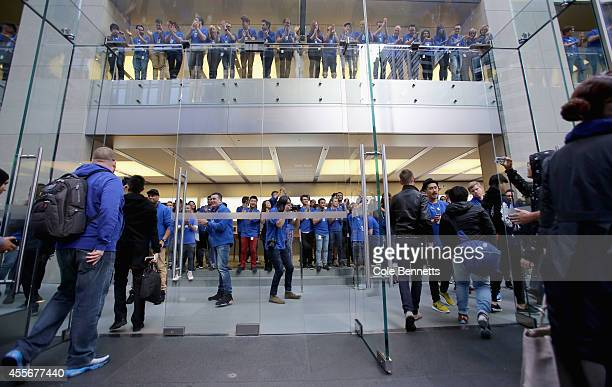 Apple employees cheer on a countdown to open doors at the Apple Store Sydney as crowds wait in anticipation for the release of the iPhone 6 at Apple...