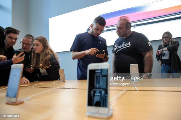 Apple employees discuss the new iPhone 8 with customers at the Fifth Avenue Apple Store September 22 2017 in New York City The new iPhone 8 and...