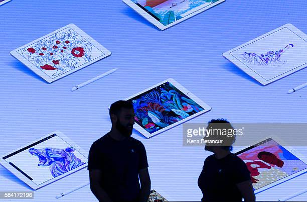 Apple employees stand next to a video screen at the new Brooklyn Apple Store during a media preview in the Williamsburg neighborhood of Brooklyn on...