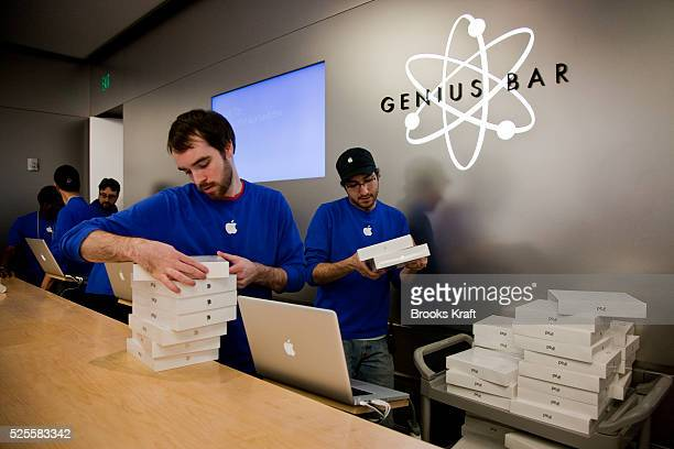 Apple employees stock the new Apple iPad 2 tablet at an Apple Store in Bethesda MD