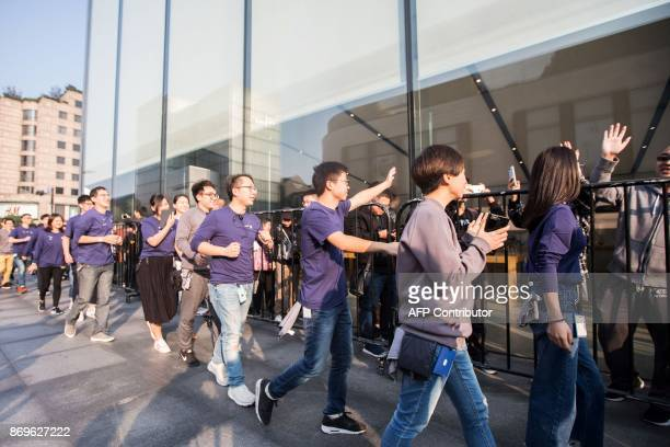 Apple employees wave to Chinese customers as they queue up outside the Apple store to get their hands on the new iPhone X in Hangzhou in China's...